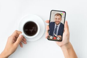 Businesswoman Making Video Call On Smartphone Talking With Coworker Indoor